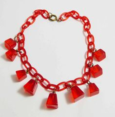 Vintage Art Deco Cherry Juice Bakelite Celluloid Necklace. Vintage authentic Art Deco period necklace featuring trapezoid shaped Bakelite pieces in bright transparent cherry juice suspended by brass j
