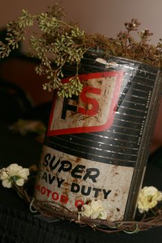 "We had a ""Hot Rod"" themed wedding. We used vintage auto and some not auto stuff for other purposes. This is a 5 quart oil can with a vase inside it, empty so that when the bride and bridesmaids came into the room they put their bouquets into the can/vase and ...instant centerpeice for head tables. 2 flower arrangements...1 price!"