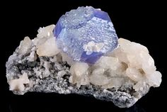 EXCEPTIONAL Fluorite crystal perched atop Calcite on matrix! A lovely, pristine Fluorite octadedron with purple and blue coloration along with modified corners and dozens of crystal faces. The 4.2 cm Fluorite is both gemmy and lustrous-glassy and the Calcites upon which it sits are in excellent condition with full terminations. From the Shangbao Mine, China. Measures 5.6 cm by 9.7 cm by 5.5 cm in total size. Price $4850