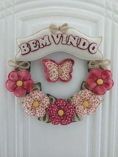 Guirlanda em arco de capim decorada com flores de tecido, placa em feltro com escrita e cores à sua escolha! Mede 35cm de diâmetro. - 8F0538