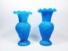 Dois vasos de opalina europeia, cor azul, formato de balaústre, corpo decorado em relevo com forma de trigo e folhas, borda revirada com babados. med: 13,5 cm e 13 cm de altura