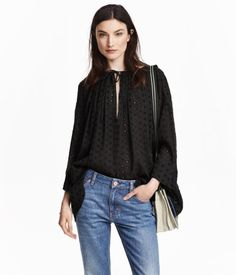Wide-cut blouse in crinkled cotton fabric with eyelet embroidery, gathers and a tie at top, and 3/4-length sleeves.