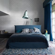 This modern blue bedroom combines industrial grey walls with deep blues for a contemporary, cosy look. The floor-standing Anglepoise lamp provides a striking touch. Image: Livingetc