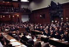 The interior of the courtroom of the Nuremberg War Crimes Trials in 1946 during the Trial of the Major War Criminals, prosecuting 24 government and civilian leaders of Nazi Germany. Visible here is Hermann Goering, former leader of the Luftwaffe, seated in the box at center right, wearing a gray jacket, headphones, and dark glasses. Next to him sits Rudolf Hess, former Deputy Fuhrer of Germany, then Joachim von Ribbentrop, Wilhelm Keitel and Ernst Kaltenbrunner