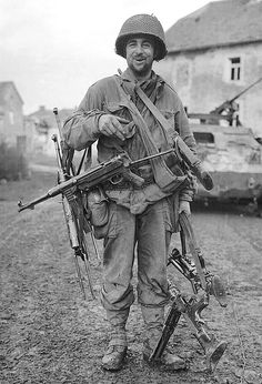 An American soldier is seen carrying several German automatic weapons. We do not know if they are battlefield pick-ups, surrendered arms, or a rather large cache of souvenirs. Maybe his satisfied smirk is a clue.