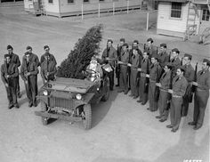 "CHRISTMAS - ARMY STYLE - Just before Santa Claus leaves his ""jeep-sleigh"" the guard of honor stands on each side presenting arms to the Christmas visitor. Camp Lee, Virginia, Quartermaster Replacement Center. December 1941."