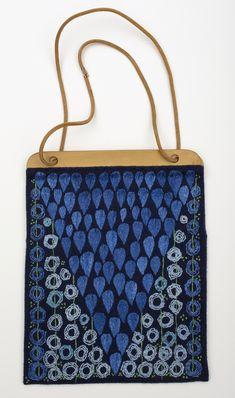 Stående rektangulär broderad väska med träbygel och läderrem som handtag. Väskan broderad i tvåtrådigt lingarn på marinblått ylletyg. I en triangel med basen mot träbygeln är droppar broderade med spetsen nedåt, i schattersöm. Utanför denna triangel, gröna stänglar i klyvsöm varpå blå ringar bestående av tre ringar i klyvsöm, är trädda. Knutsöm främst i kanterna. Väskan fodrad med fodertyg (kontsiden?) i marinblått.    Se också skärp KLH.A2:621.