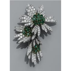 AN EMERALD AND DIAMOND BROOCH Designed as three flower heads, set to the stamen with circular-cut and oval-shaped emeralds, to pavé-set brilliant-cut diamond petals.