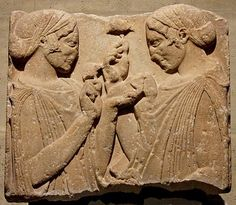 "o-called ""Exaltation de la Fleur"" (exaltation of the flower), fragment from a grave stele: two women wearing a peplos and kekryphalos (hairnet), hold poppy or pomegranate flowers, and maybe a small bag of seeds. Parian marble, c. 470–460 BC. From Pharsalos, Thessaly."