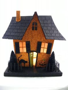 Putz Halloween Glitter House ~ Pressed cardboard embellished with orange and black glitter. Silhouettes of a flying witch and tree adorn the sides along with bottle brush trees.