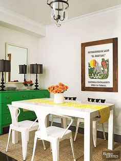 The dining room in the apartment is a small nook between the kitchen and living room area and the bedroom. Although small, smart design choices make it hardworking and stylish. The art on the wall -- a grain sack the couple picked up for 20 cents while in Guatemala -- is the centerpiece of the space. In a furnishings twist, the green buffet is actually a dresser. The homeowners needed something in a particular size and the dresser fit the bill. With a paint makeover and new knobs, it's a…