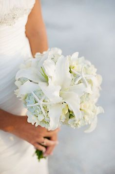Chic starfish accent a bouquet of hydrangeas and lilies. Beach wedding bouquet