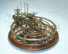 An orrery is a mechanical device that illustrates the relative positions and motions of the planets and moons in the Solar System in a heliocentric model. Though the Greeks had working planetaria, the first orrery that was a planetarium of the modern era was produced in 1704, and one was presented to the Earl of Orrery — whence came the name. They are typically driven by a clockwork mechanism with a globe representing the Sun at the centre, and with a planet at the end of each of the arms.