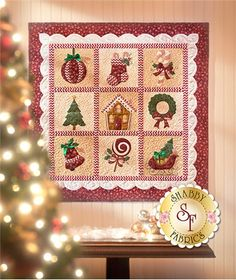 "Christmas Keepsakes BOM - Pre-fused/Laser: Christmas Keepsakes is a 10-month Block of the Month quilt designed by Jennifer Bosworth exclusively for Shabby Fabrics. This darling 36"" x 36"" quilt was sewn with Maywood Studio fabrics and features appliqued blocks in classic Christmas shapes and colors. The pretty scalloped inner border and embellishments add the perfect finishing touch to this adorable holiday wall hanging."