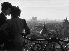 """C'est une photographie réalistes """"Les amoureux de la bastille  """" , crée en 1957 , photographié par Willy Ronis. On y voit un couple , qui s'embrasse sous une vue qui surplombe   Paris , la ville romantique ,la ville des amouruex .  La photo est en noir et blanc , L'auteur nous montre a travers cette photo le semtiment de l'amour .Source : internaute week end ."""
