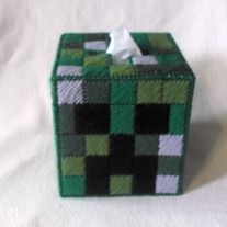 "Up for sale is a plastic canvas tissue box cover/Kleenex cozy featuring a Creeper face inspired by ""Minecraft."" Each of the box's 4 sides has a slightly different style of Creeper. The variations of color are done in 3 different shades of green, as well as gray and black. This Kleenex cozy ..."