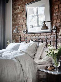 Cărămidă expusă, tapet cu motive florale și o bucătărie rustică într-un apartament de trei camere din Suedia.