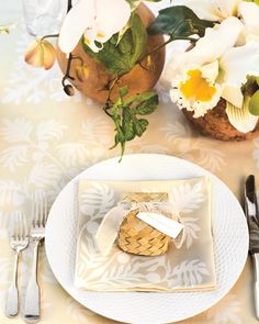"""At each placesetting, a favor box woven from lauhala straw rests on a breadfruit-printed napkin.The Details: Favor box, from $2;alohagiftsfromhawaii.com.Ribbon (on favor box), $3/5 yds; save-on-crafts.com. International Silver Co. """"1810"""" flatware, $1,320 for a 5-piece setting; lifetimesterling.com. Pillivuyt """"Basketweave"""" dinner plate, $112 for 4; williams-sonoma.com."""