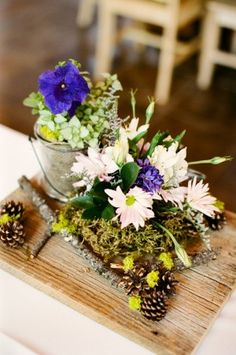 Use a wooden board as the platform to any rustic centerpiece | Photography by http://michellecrossphotography.com/