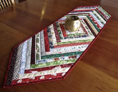 This colorful table runner is made from a multitude of fabric selvedges with a Christmas theme: there are stars, holly leaves, candy canes, Christmas trees, snow scenes, Santas, birds, red berries and more. In the center there is a small square of dark red fabric with ivory stars. This table runner is reversible: for the backing I used a print with little red-hatted Christmas gnomes lined up against an off-white background. The binding is a dark red fabric with tiny black stars and holly… Etsy Christmas, Christmas Deco, Christmas Trees, Quilted Table Runners Christmas, Christmas Runner, Fall Placemats, Table Runner And Placemats, Winter Table, Snow Scenes