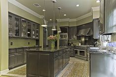 Dark gray cabinets and green walls, backsplash.