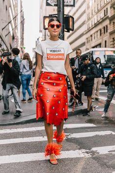 Maneiras nada básicas de usar t-shirt. Blusa branca, saia de couro estampada, sandália laranja com plumas