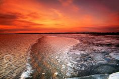 Red sunset in Finland over half frozen sea by behindmyblueeyes, $29.00