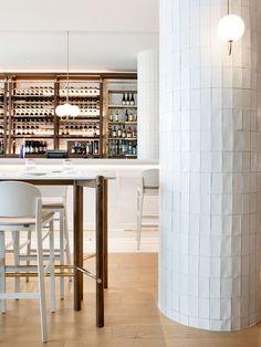 restaurante em tons claros e detalhes em madeira e dourado