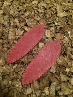 These earrings are a beautiful maroon colored leather that are hand cut in the shape of a feather. They hang at 4.25 and are mounted on antique