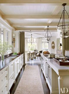 The home was renovated by Meyer & Meyer Architecture and Interiors and decorated by McAlpine Booth & Ferrier Interiors. Lanterns by Formations are suspended in the main kitchen, which has cabinetry painted in a Benjamin Moore off-white, a Rohl sink with Lefroy Brooks fittings, and a Gaggenau cooktop and oven.