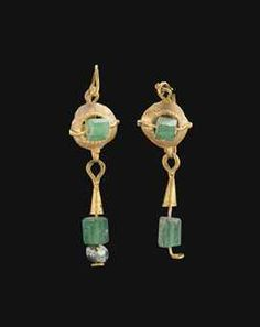 A PAIR OF ROMAN GOLD AND GLASS EARRINGS  CIRCA 2ND-3RD CENTURY A.D.  Each with an open dome, the inner border with a fringe of twisted wire, bisected by a plain wire threaded through a faceted green glass bead, a loop above and below, the upper joined to the plain earwire, the lower suspending a conical element topped with a granule, with a wire threaded below through a faceted green glass bead and a spherical glass bead (one preserved) Longer: 1 7/8 in. (4.8 cm.) high (2)