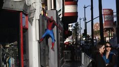 A person dressed like the character of Spiderman hangs from a wall in Hollywood, California March 12, 2014. REUTERS/Mario Anzuoni  Image 5...