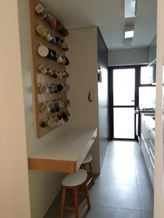 Coleção de canecas decora a parede da cozinha deste pequeno apartamento.
