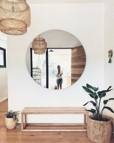 Simple entryway- ikea rattan pendant, oversized round mirror, minimalist wood bench, plants, white walls