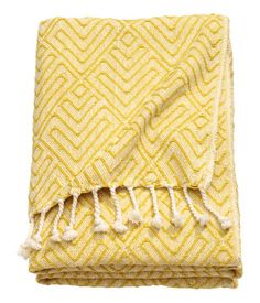 Jacquard-weave throw in cotton fabric with fringe on short sides.