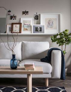 Ei bildehylle med innrammede bilder og kunst over en sofa. Mindre bilder er festet på veggen med dekorativ teip.
