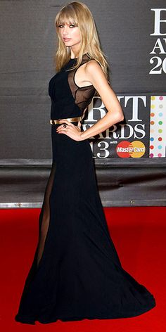 Black Elie Saab gown with sheer panels and a gold belt.