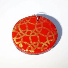 Pendentif rouge avec motifs anneaux dorés