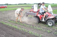 Jim Eklund drives as agronomist Frank Forcella blasts small weeds away with pressurized grit from a prototype of PAGMan (Propelled Abrasive Grit Management)