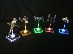 """Star Wars X-Wing Miniatures Ship Base LED by PushTheLimitLED. """"Give your X-wing squad some real table presence! Table your Rebel squad with ice blue, field your U-Boats in scummy orange, or fly your Imperial swarm with menacing red!"""" Purchase your LED upgrade kits in the following color choices: Red, Orange, Yellow, Green,Blue, Pink, White."""