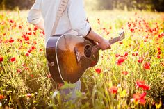Playing guitar in a field of poppies. Lovely.