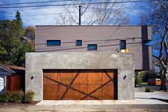 18 Inspirational Examples Of Modern Garage Doors // Angular strips of steel mesh break up the square weathered steel panels of this garage door and add an artistic flair to the home.