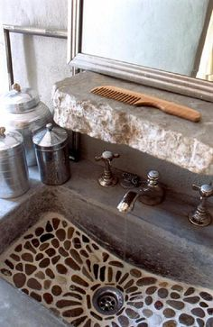 Use broken edged granite for shelving, bracketed for support underneath       - ---We love this mosaic pebble stone bathroom sink with a rough stone built in shelf