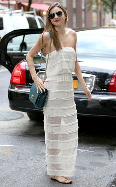 Miranda Kerr was a VISION in a partially sheer, cream-colored maxi dress with an emerald bag and classy aviator sunnies!