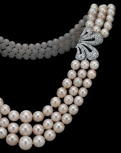 A three-strand natural pearl, cultured pearl and diamond necklace detail