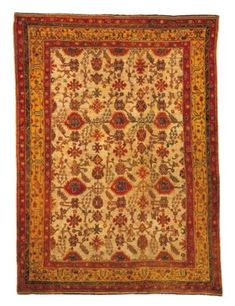 USHAK CARPET  WEST ANATOLIA, CIRCA 1890  The ivory field scattered with stylised floral motifs and bold stylised palmettes issuing angular floral and leafy vine in a mustard-yellow border of angular vine meander between dusty pink floral meander, barber-pole and zigzag stripes, selvages original, ends complete 16ft.7in. x 12ft.3in. (504cm. x 373cm.)