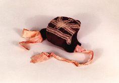 Die Kinderhaube für Jungen besteht aus fliederfarbener Atlasseide mit aufgenähten Tüllstreifen und rosa Bändern. Sechsteilig genäht. Die Haube stammt angeblich aus Holstein.