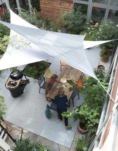 Des voiles d'ombrage accrochés au-dessus d'une cour intérieure, une façon de rafraîchir l'été ! Castorama