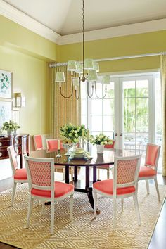 The homeowners wanted to have a fresh, bright dining room, so designer Ashley Whittaker helped them pick a showstopping lettuce green shade for the shiny lacquered walls and then kicked it up a notch with bright coral upholstered dining chairs. Painted lantern sconces and a sleek, four-arm, unlacquered brass chandelier play off the casual mood established by the sweet/tart color scheme.    Love it? Get it! Chair fabric (back): Volpi (custom colorway) by Quadrille. Wall paint: Young Wheat