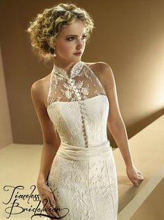 Novia D'Art Jessy  Fitted lace Novia D'art Jessy Wedding Dress featuring high neck. Button up front extends to a beautiful sheer lace back with chiffon sash.    Was €2,100, Now €899    Significantly Reduced.